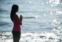 Силуэт женщины медитирующей на пляже в солнечный день — стоковое фото