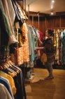 Mulher selecionando roupas em cabides na loja de roupas — Fotografia de Stock