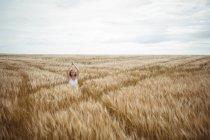 Mulher com as mãos levantadas sobre a cabeça em posição de oração em pé no campo no dia ensolarado — Fotografia de Stock