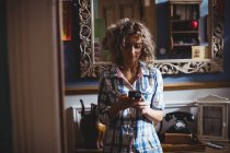 Beautiful woman using mobile phone at home — Stock Photo