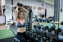 Красивая женщина поднимает гантели в спортзале — стоковое фото