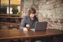 Metà sezione di uomo utilizzando il computer portatile al bar — Foto stock