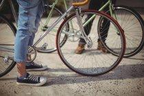 Femme debout avec vélo sur la route — Photo de stock