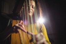 Attentive woman playing a harp in music school — Stock Photo