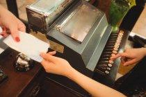 Кассирша принимает оплату в кассе — стоковое фото