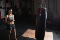 Женщина-боксер смотрит на боксерскую грушу в фитнес-студии — стоковое фото