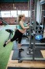 Femme enceinte faisant de l'exercice avec barre de fitness dans la salle de gym — Photo de stock