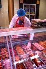 Butcher checking the meat display in butchers shop — Stock Photo