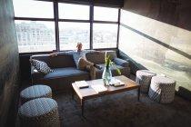 Hombre de negocios despreocupado sentado en el sofá en la oficina - foto de stock