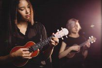 Belle donne che suonano una chitarra nella scuola di musica — Foto stock