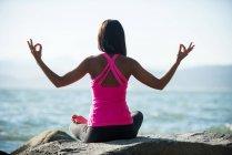 Задний вид женщины, практикующей йогу на камне в солнечный день и показывающей жест мудры — стоковое фото