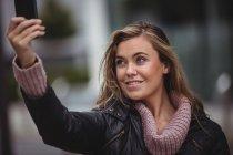 Красиві усміхається жінка беручи selfie смартфон на вулиці — стокове фото