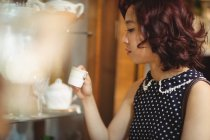 Stylish woman selecting a cup in a antique shops — Stock Photo