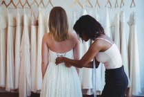Woman trying on wedding dress with the assistance of fashion designer in the studio — Stock Photo
