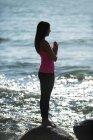 Боковой вид женщины, сидящей на камне в солнечный день — стоковое фото