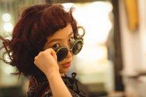 Портрет стильной женщины, смотрящей на солнечные очки — стоковое фото