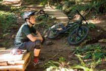 Задумчивый велосипедист сидит в лесу в солнечный день — стоковое фото