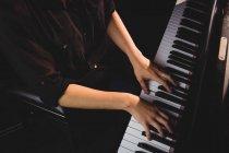 Середньої частини студентка грати на фортепіано в студії — стокове фото