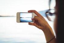 Крупный план женщины, фотографирующей городской пейзаж на мобильный телефон — стоковое фото