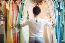 Mulher selecionando uma roupa de cabides na loja boutique — Fotografia de Stock