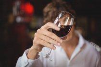 Бармен смотрит на бокал красного вина за барной стойкой — стоковое фото