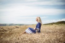 Вид збоку безтурботним блондинка жінка, що сидить у сфері — стокове фото
