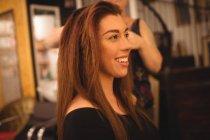 Junge Brünette stylt ihre Haare im Schönheitssalon — Stockfoto