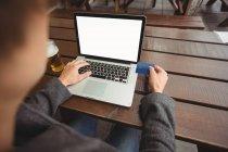 Hombre haciendo compras en línea con tarjeta de crédito en el ordenador portátil en el bar - foto de stock