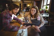 Kundin zeigt Kellnerin im Fahrradladen digitales Tablet — Stockfoto