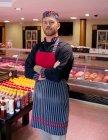 Портрет м'ясника, стоячи в магазині м'ясо з обіймами перетнула — стокове фото