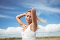 Attractive blonde woman standing in field with hands in hair — Stock Photo