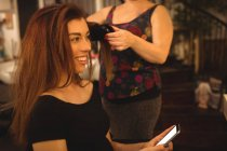 Жінка, використовуючи мобільний телефон під час отримання волосся випрямлену в салоні волосся — стокове фото