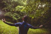Возбужденный спортсмен с протянутыми в лесу руками — стоковое фото