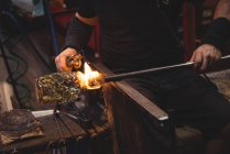 Обрезанное изображение стеклодува, формирующего расплавленное стекло на стекольном заводе — стоковое фото