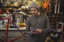 Механік за допомогою мобільного телефону в магазин велосипедів — стокове фото