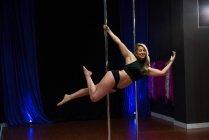Beautiful Pole dancer practicing pole dance in studio — Stock Photo