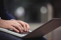 Sección media del hombre de negocios usando el ordenador portátil - foto de stock