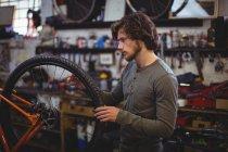 Механік вивчення велосипедного колеса у майстерні — стокове фото