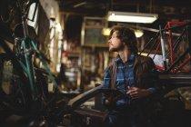 Mécanicien utilisant une tablette numérique lors de la réparation du vélo en atelier — Photo de stock