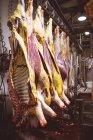 Carne vermelha descascada pendurada na arrecadação do talho — Fotografia de Stock