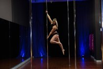 Attractive Pole dancer practicing pole dance in studio — Stock Photo