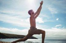 Человек, выполняющий упражнения на растяжку на пляже — стоковое фото