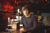 Ritratto di uomo con un bicchiere di birra al bancone del bar — Foto stock