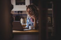 Beautiful woman using laptop while having coffee in kitchen at home — Stock Photo
