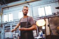 Soffiatore di vetro che modella un vetro fuso alla fabbrica di soffiaggio del vetro — Foto stock