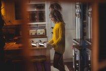Mulher bonita usando tablet digital enquanto toma café na cozinha em casa — Fotografia de Stock