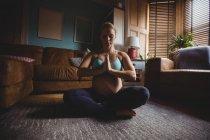 Привлекательная беременная женщина, занимающаяся йогой в гостиной — стоковое фото