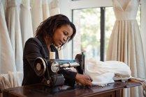 Styliste de mode sur la machine à coudre dans l'atelier de couture — Photo de stock
