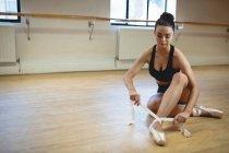 Балерина в балетной обуви на полу в студии — стоковое фото