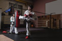 Спортсменка і спортсмен практикуючих карате з боксерської груші в студії — стокове фото